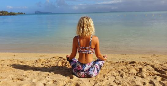 A lady on a beach wearing Yoga wear for women made from recycled plastic bottles